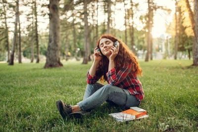 Female student in headphones sitting on the grass