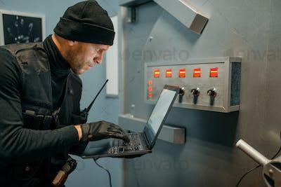 Robber with laptop trying to open the vault door