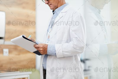 Senior Doctor writing on Clipboard