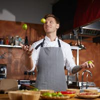 Chef Juggling Fruits in Kitchen
