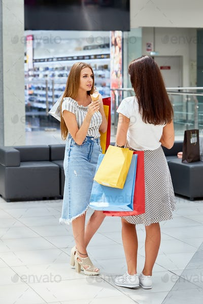 Two Girls with Shopping Bags Chatting