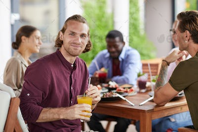 Handsome Man Enjoying Lunch with Friends in Cafe