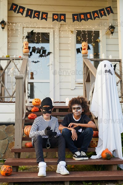 Two Boys Posing by Decorated House on Halloween