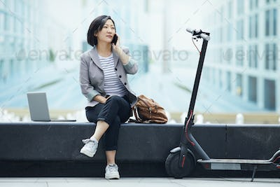 Asian Woman Speaking by Phone in City