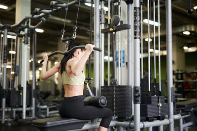 Fit Woman using Exercise Machines in Gym