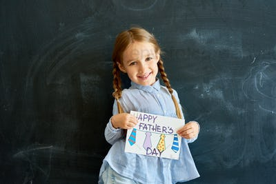 Happy Little Girl Holding Greeting Card for Fathers Day