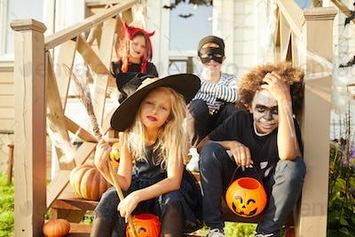 Kids Sitting on Porch on Halloween