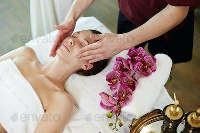 Woman Enjoying Facial Massage in SPA