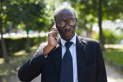 African-American Businessman Speaking by Phone Outdoors