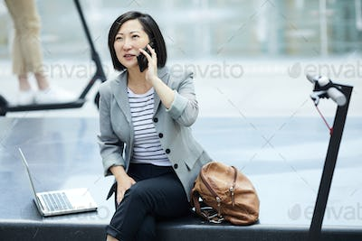 Asian Woman Speaking by Smartphone in City