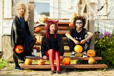 Three Kids Posing by Decorated House on Halloween