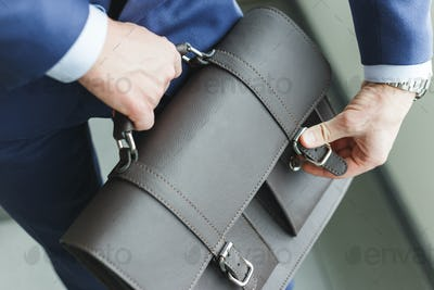 Man in suit fastens briefcase. New vacancy for the position