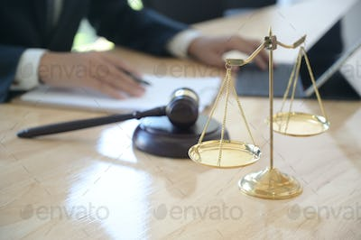 Concept of justice, Lawyer holding a hammer pretending to hit on a wooden tray put on the desk.