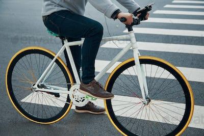 Crop man riding bicycle near crosswalk