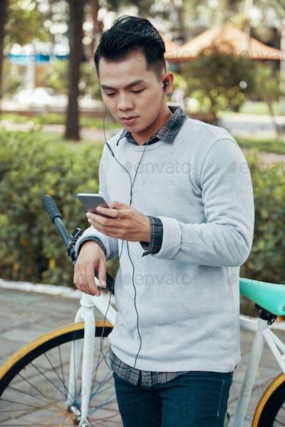 Asian men in earphones using smartphone near bicycle