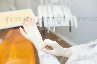 Crop dentist putting on white gloves