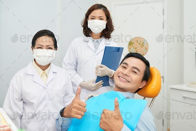 Smiling patient and doctors in dental office