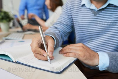 Crop casual man writing in notepad