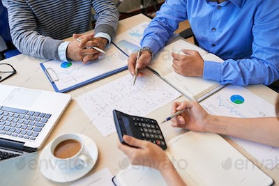 Crop colleagues making report and calculating