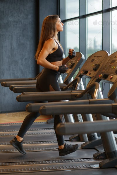 sportswoman running on treadmill in gym