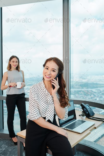 Young business lady talking on phone