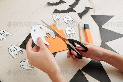 Woman cutting cute ghosts out of paper