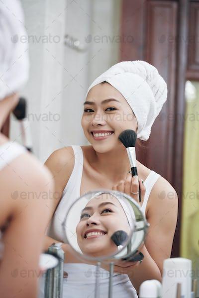 Coquettish ethnic woman doing makeup in bathroom