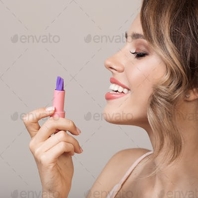 Attractive Smiling Woman Holding Lipstick In Hand.