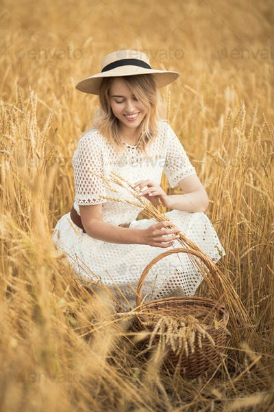 Young Attractive Woman And Golden Wheat Field. Harvest Concept.