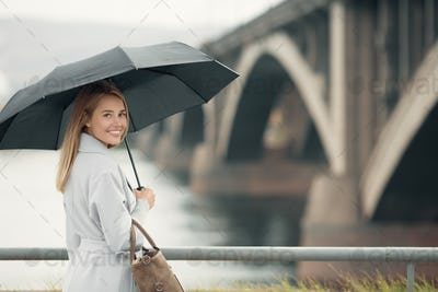 Young Woman In Blue Coat Holding Umbrella. Autumn City