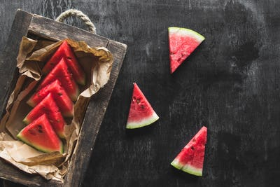 Watermelon in a wooden box. Sliced to pieces of watermelon. On a wooden background