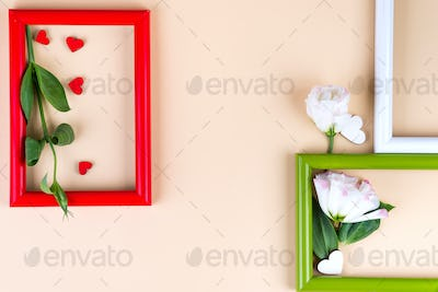 Empty color frames, red hearts and flowers eustoma on beige paper background with copy space. Love