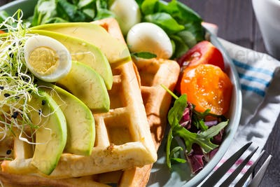 Belgian Waffles with avocado, eggs, micro green and tomatoes with orange juice close-up. Perfect