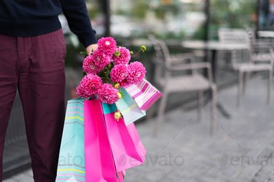 Boyfriend waiting for his girlfriend near cafe and holding flowers bouquet and bunch of pink gift