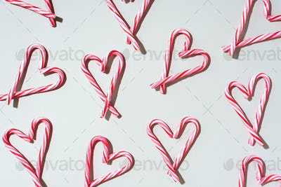 Pattern with hearts made of Christmas candy canes on grey background. Top view. Flat lay. Love