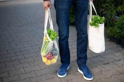 Man is holding mesh shopping bag with begetables without plastic bags at farmers market. Zero waste