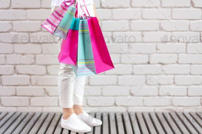 Shopping concept. Girl holding bunch of shopping bags with purchases near brick background. Copy
