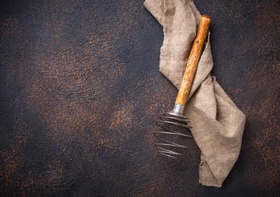 Vintage wooden whisk on old rusty background