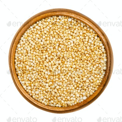 Puffed quinoa in wooden bowl over white
