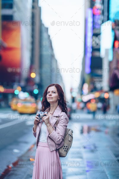 Attractive tourist with retro camera in NYC