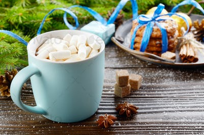 Christmas background of blue hot chocolate mug with marshmallows