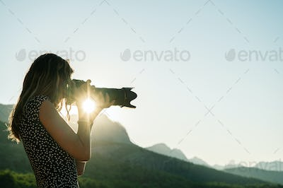 Young female photographer taking photos of beautiful nature