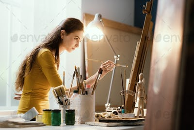 Creative woman painting on canvas in the studio