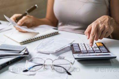 Stressed young woman checking bills, and calculating expenses