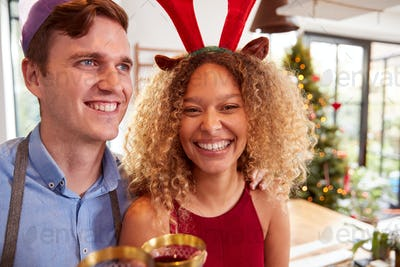 Couple Wearing Fancy Dress Antlers And Paper Hat Drink Wine Whilst Cooking Dinner On Christmas Day
