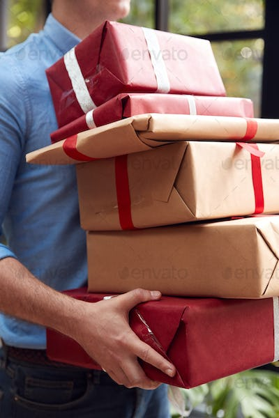 Close Up Of Man Carrying Pile Of Christmas Presents Standing By Tree At Home