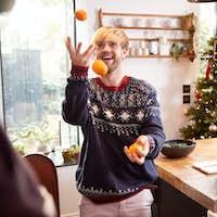 Man In Kitchen Juggling Satsumas Whilst Preparing Christmas Dinner