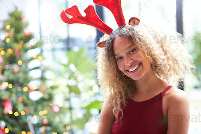 Portrait Of Woman Wearing Fancy Dress Antlers Standing Next To Christmas Tree At Home