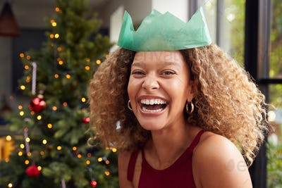 Portrait Of Smiling Woman Wearing Paper Hat Standing By Tree At Home
