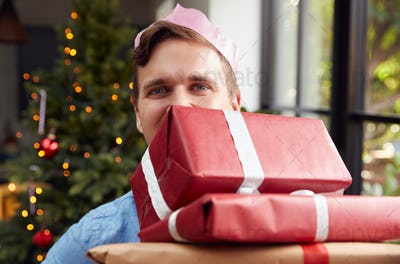 Portrait Of Man Wearing Paper Hat Carrying Pile Of Christmas Presents Standing By Tree At Home